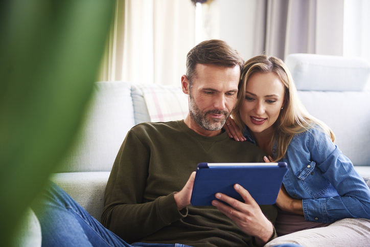 couple reviewing finances on tablet